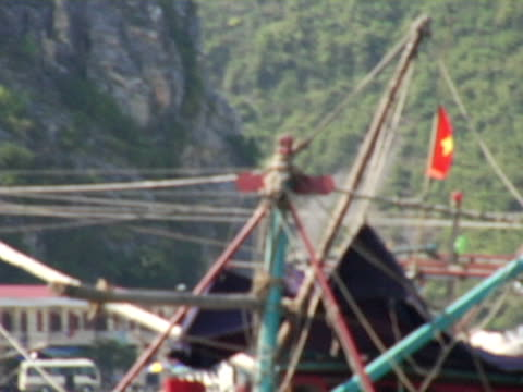 side pov, vietnam, halong bay, passing boat with vietnamese flag in harbor - anchored stock videos & royalty-free footage