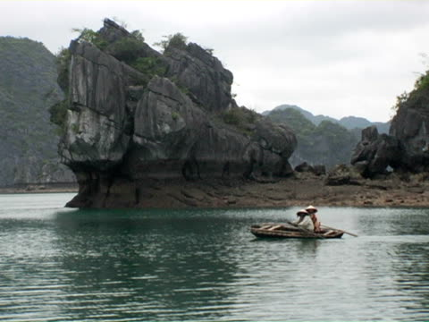 ms, vietnam, halong bay, two people in boat passing limestone cliff - halong bay stock videos and b-roll footage