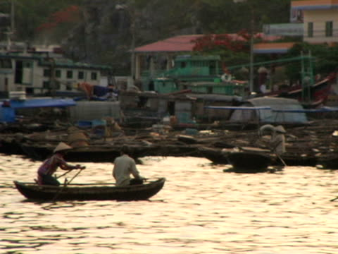 ms, vietnam, halong bay, woman rowing traditional boat towards shore of harbor - halong bay stock videos and b-roll footage