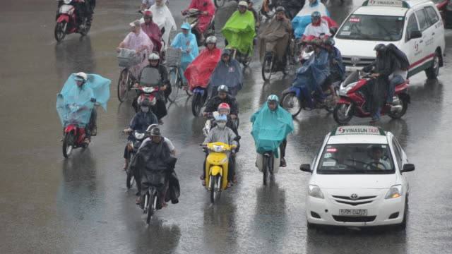 vietnam, ho chi minh city, bicycle and motorcycle street traffic in heavy rain - moped stock videos and b-roll footage