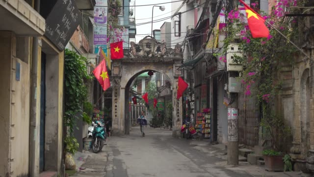 vietnam iconic old town street with vietnamese red flags and old gate at van phuc, hanoi - newly industrialized country stock videos and b-roll footage