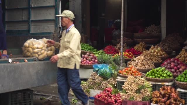 vietnam thien thuat food market. men carrying potatoes sack - bazar delle spezie video stock e b–roll