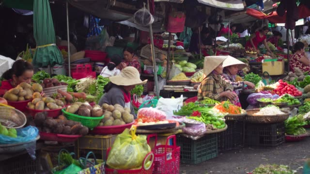vietnam vegetables street market. iconic image of women with traditional clothing and conical hat selling - traditional clothing stock videos & royalty-free footage