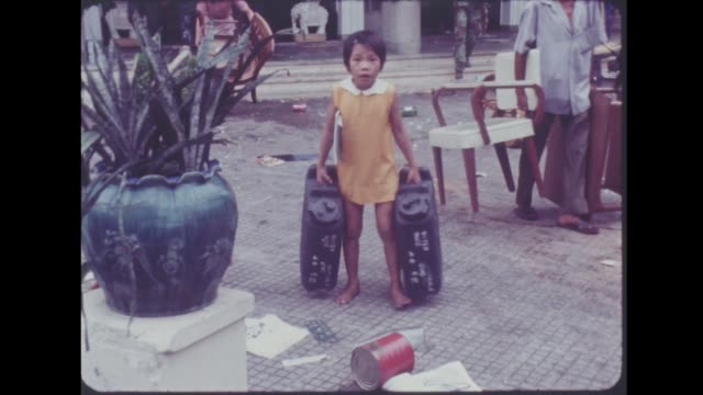 fall of saigon:; south vietnam: saigon: ext gv high angle of people looting man towards with table gv people with various objects solider along with... - group of objects stock videos & royalty-free footage