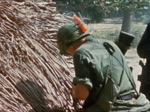 vietnam war us soldier setting fire to grass hut in vietnamese village / vietnam - grass hut stock videos & royalty-free footage