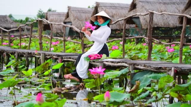 vídeos y material grabado en eventos de stock de mujeres de vietnam mantenga lotus sentado en el campo de lotus, vietnam - posa del loto