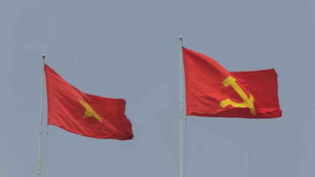ws ld vietnamese and communist flags waving / vietnam - communist flag stock videos and b-roll footage