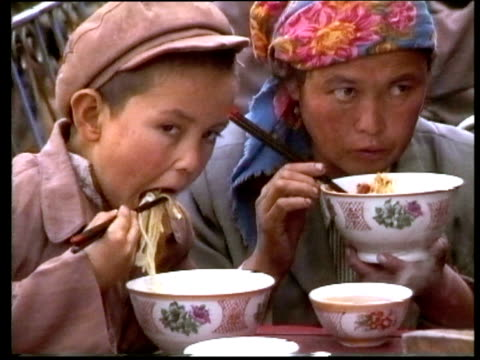 vietnamese boy wearing cap and eating noodles next to mother vietnam - two generation family stock videos & royalty-free footage