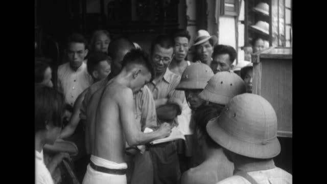 vietnamese civilians interact with imperial japanese army soldiers as city life continues under japanese control and transportation and commerce... - indocina video stock e b–roll