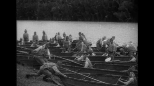 Vietnamese civilians watch as Imperial Japanese troops wear life jackets when they conduct boat drills on the Mekong River