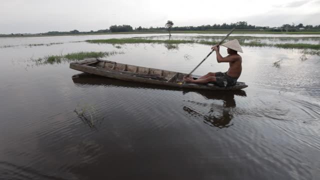a vietnamese fisherman paddles his boat along the mekong delta near ho chi minh city, vietnam. - 麦わら帽子点の映像素材/bロール