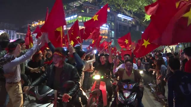 Vietnamese football fans celebrating on the street with the national flags after their Under 23 national team defeat Under 23 Qatar at the semi final...