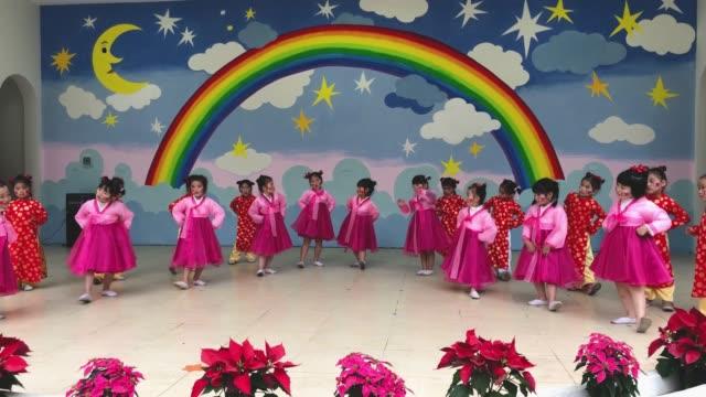 vietnamese girls in traditional ao dai dresses perform a dance at the vietnamnorth korea friendship kindergarten a school that was gifted to vietnam... - 首脳会議点の映像素材/bロール