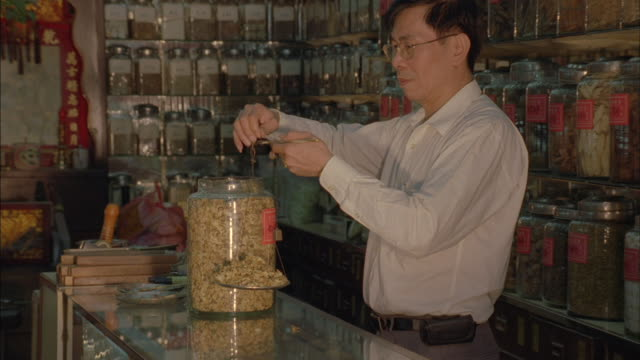 A Vietnamese grocer measures a product on a scale.
