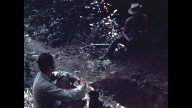 vietnamese man detained by 1st cav patrol sits and then hands over his id card he had neither weapon nor rucksack gi holding an m16 watching him a... - m16 stock videos & royalty-free footage