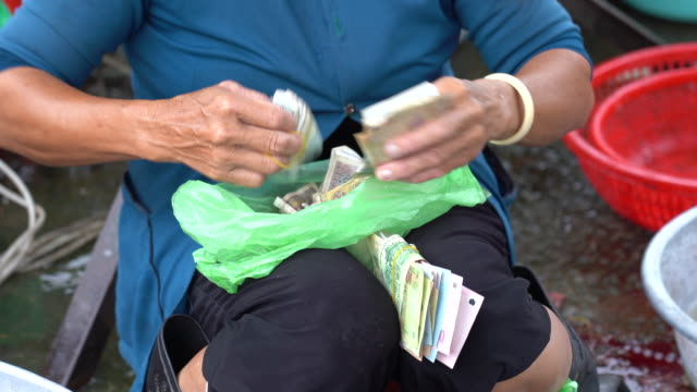 vietnamese marketers are counting the cash generated by selling products in the bazaar. - money makes the world go around stock videos and b-roll footage