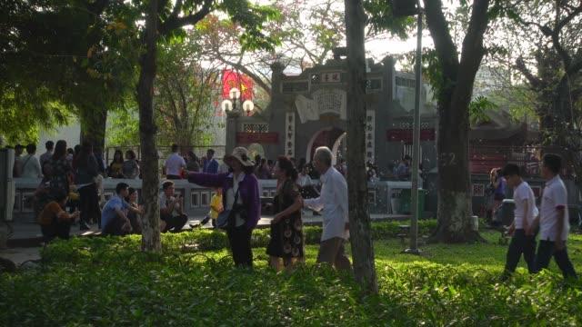 vietnamese people celebrating tet next to cau the huc bridge, at ngoc son jade mountain buddhist temple. hoan kiem lake - traditionally vietnamese stock videos & royalty-free footage