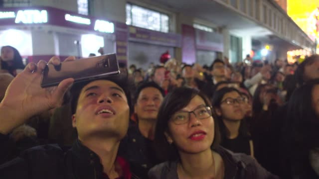 vietnamese people looking at fireworks during new year tet celebration. hanoi hoan kiem old quarter district - traditionally vietnamese stock videos & royalty-free footage