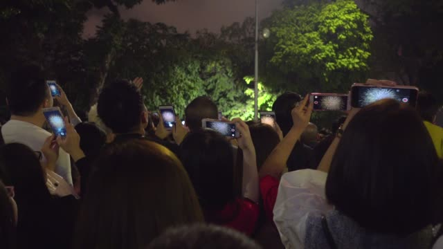 vietnamese people using phone to take pictures of the fireworks during tet vietnamese new year celebration. hanoi hoan kiem old quarter district - chinese culture stock videos & royalty-free footage