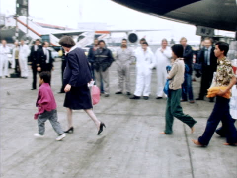 Vietnamese refugees arrive in United Kingdom ENGLAND London Heathrow Airport aircraft taxis towards MS Vietnamese passengers off plane and along MS...