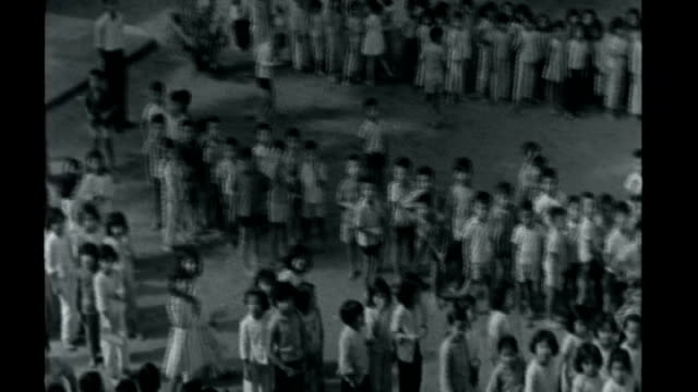 Vietnamese war orphan opens orphanage X07076501 / ITN Reports 7 July 1965 Saigon W footage Various views of Vietnamese orphans in yard and eating in...