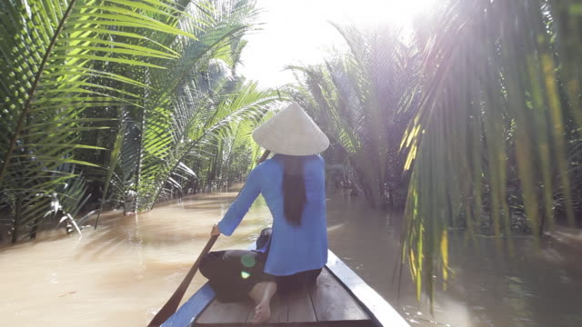 a vietnamese woman paddles a boat past palm trees along the mekong delta near ho chi minh city, vietnam. - ho chi minh city stock videos & royalty-free footage