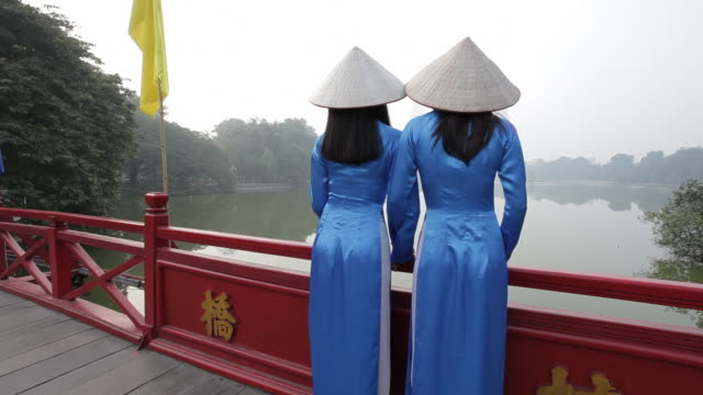 vietnamese women wear öo d_i and non la as they look at ho kiem lake in hanoi. - traditional clothing stock videos & royalty-free footage