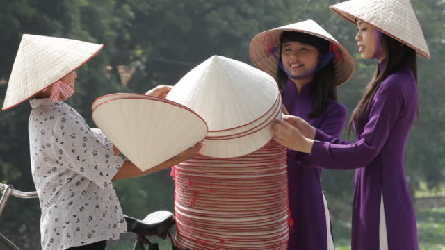 vietnamese women wear traditional ao dai as they negotiate with a non la merchant - ベトナム点の映像素材/bロール
