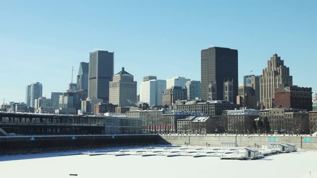 冬の晴れた日に桟橋から金融街まで見ているヴューモントリオールとダウンタウンウィンタースカイライン - モントリオール旧市街点の映像素材/bロール