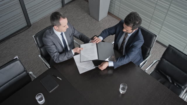 CS View above the table in conference room and two businessmen signing a contract and shaking hands