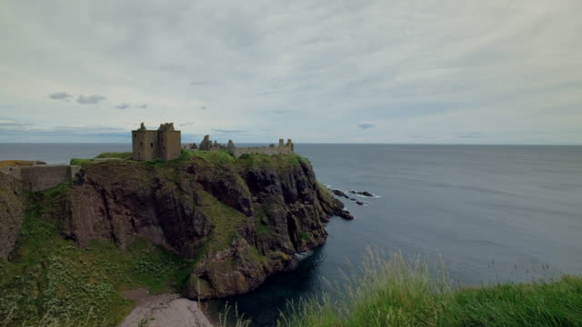 vídeos y material grabado en eventos de stock de view across a calm north sea with the ruins of dunnottar castle perched on high sea cliffs - vivienda en roca