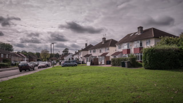 View across a green looking down a street of classic 1950's suburban semi-detached houses in a residential area of North London