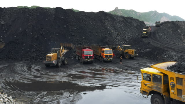 view across a large open cast coal mine and coal pile that feeds and powers baogang iron and steel plant in baotou inner mongolia china mining trucks move coal spoil and slag - coal mine stock videos & royalty-free footage