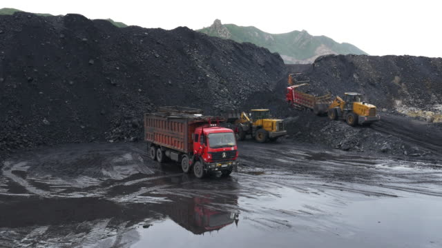 View across a large open cast coal mine and coal pile that feeds and powers Baogang Iron and Steel plant in Baotou Inner Mongolia China Mining trucks move coal spoil and slag