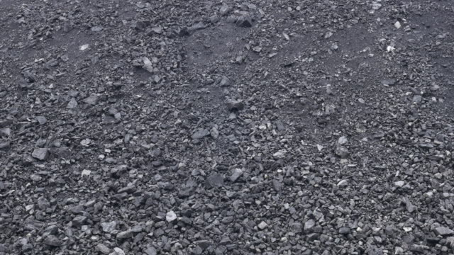 vidéos et rushes de view across a large open cast coal mine and coal pile that feeds and powers baogang iron and steel plant in baotou inner mongolia china mining trucks move coal spoil and slag - charbon