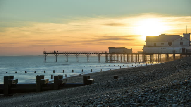 a view across a pebble beach looking towards a traditional seaside pier as the sun sets in bognor regis, a coastal holiday resort on the south coast of england - jetty stock videos & royalty-free footage
