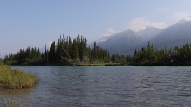 View across fast flowing river to distant forest and mountains