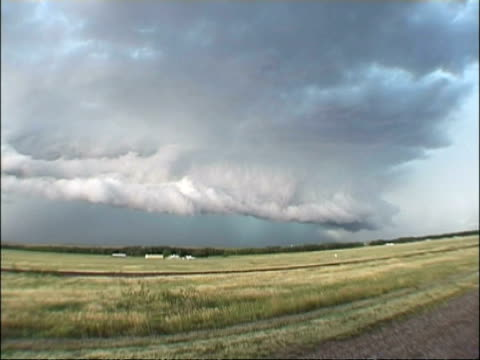 WA View across fields, large storm clouds over horizon, lightning flashes