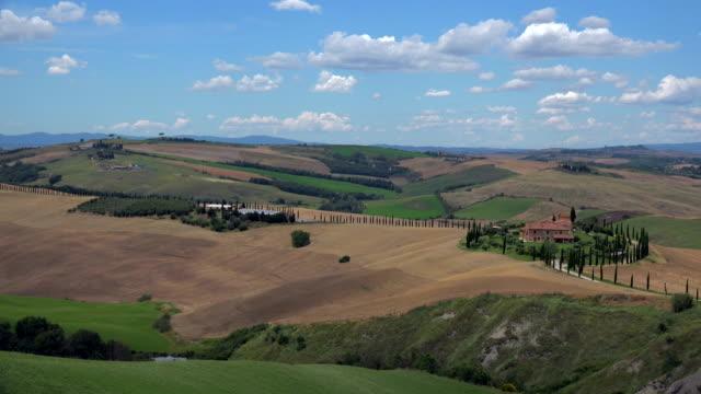 view across fields with country house, landscape of crete senesi, province of siena, tuscany, italy - toscana bildbanksvideor och videomaterial från bakom kulisserna