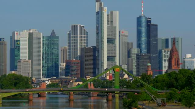 View across Main River towards Floesserbruecke Bridge with Skyline of Frankfurt am Main, Hesse, Germany