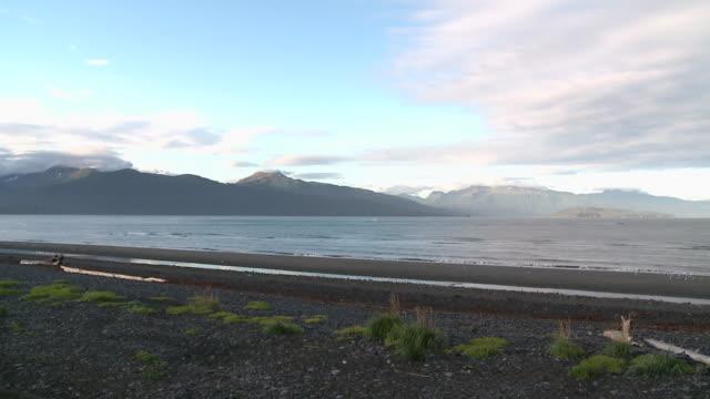 """view across resurrection bay from beach near seward,  kenai peninsula, alaska, with resurrection peninsula mountain range across  the water."" - kenai peninsula stock videos & royalty-free footage"