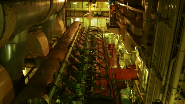 stockvideo's en b-roll-footage met view across the engine room of a container ship at sea with one of the world‰ûªs largest diesel engines at work - machinekamer