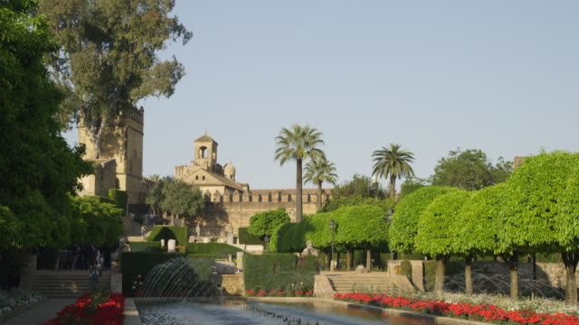 ms view across the gardens and fountains to the main part of the alcazar palace with the torre de los leones (tower of the lions) and the torre de homenaje (tower of homage). the latter has gothic features. - main tower stock-videos und b-roll-filmmaterial