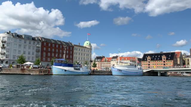 a view across the harbour looking towards copenhagen, a boat passes, denmark - öresundregion stock-videos und b-roll-filmmaterial
