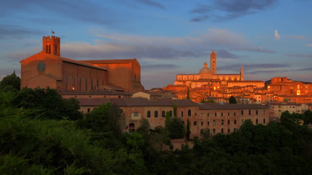 view across the old town towards basilica di san domenico and santa maria assunta cathedral and campanile in siena, tuscany, italy - basilica video stock e b–roll