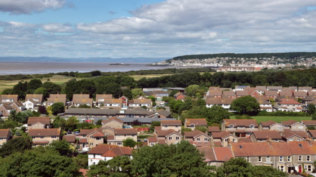 view across the roofs of uphill village with weston-super-mare and the bristol channel in the distance - weston super mare stock videos and b-roll footage