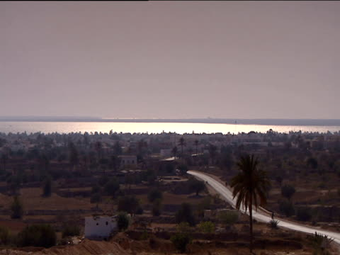 view across town to coast sea glimmering in the evening sun tunisia - tunisia video stock e b–roll