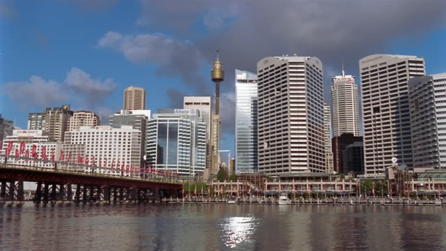 View across water of Darling Harbour wharf and Sydney Tower rising over skyscrapers in Central Business District / monorail and pedestrians crossing Pyrmont Bridge / Sydney, Australia