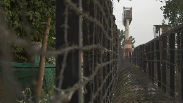 view along a barb wire fence towards a guard tower - jammu e kashmir video stock e b–roll