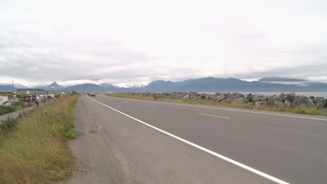 """view along busy homer spit road towards snow capped mountains of kachemak bay state park and wilderness park, homer, kenai peninsula, alaska."" - homer alaska stock videos & royalty-free footage"